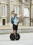 Den unga lyckliga turist- mannen med ryggsäckridningstaden turnerar segway köra den lyckliga och upphetsade besöka Madrid slotten Royaltyfria Bilder