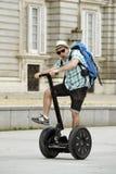 Den unga lyckliga turist- mannen med ryggsäckridningstaden turnerar segway köra den lyckliga och upphetsade besöka Madrid slotten Royaltyfri Foto