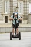 Den unga lyckliga turist- mannen med ryggsäckridningstaden turnerar segway köra den lyckliga och upphetsade besöka Madrid slotten Royaltyfria Foton