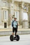 Den unga lyckliga turist- mannen med ryggsäckridningstaden turnerar segway köra den lyckliga och upphetsade besöka Madrid slotten Arkivfoton