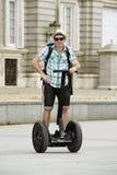Den unga lyckliga turist- mannen med ryggsäckridningstaden turnerar segway köra den lyckliga och upphetsade besöka Madrid slotten Arkivbild