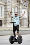 Den unga lyckliga turist- manridningstaden turnerar segway köra den lyckliga och upphetsade besöka Madrid slotten Arkivfoto