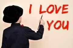 Den unga målaren med borstehandstilen ÄLSKAR JAG DIG på väggen Fotografering för Bildbyråer