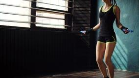 Den unga målmedvetna allvarliga kvinnliga boxaren, i slåget in, förbinder nävehänder som hoppar på överhopprep i idrottshall stock video
