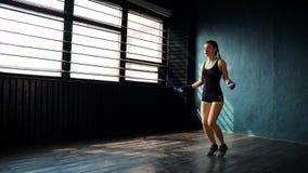 Den unga målmedvetna allvarliga kvinnliga boxaren, i slåget in, förbinder nävehänder som hoppar på överhopprep i idrottshall arkivfilmer