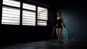 Den unga målmedvetna allvarliga kvinnliga boxaren, i slåget in, förbinder nävehänder som hoppar på överhopprep i idrottshall lager videofilmer