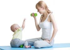 Den unga mamman med behandla som ett barn göra gymnastik, och kondition övar Royaltyfria Bilder