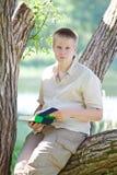 Den unga manen (eleven, deltagaren) läser boka på floden Arkivfoton