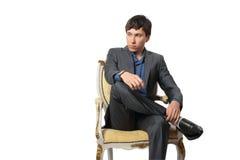 Den unga manen sitter i en stol Royaltyfri Fotografi