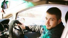 Den unga manliga chauffören sitter rymma hans hand bak hjulet i salongen av hans bil Royaltyfria Bilder
