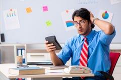 Den unga manliga finansiella chefen som arbetar i kontoret arkivfoton