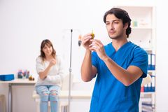 Den unga manliga foctoren och den kvinnliga patienten i blodtransfusionbegrepp royaltyfri foto