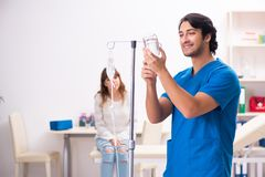 Den unga manliga foctoren och den kvinnliga patienten i blodtransfusionbegrepp royaltyfri fotografi