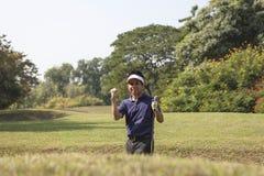 Den unga manliga grå färgen för golfspelare flåsar gå i flisor golfboll ut ur en sa Royaltyfri Fotografi