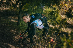 Den unga manliga idrottsman nen i skog fotvandrar traill med nordiska gå poler Royaltyfria Bilder