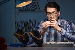 Den unga manliga juveleraren som arbetar på natten i hans seminarium Arkivbild