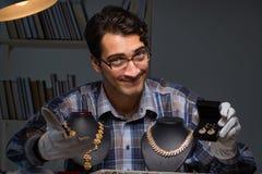 Den unga manliga juveleraren som arbetar på natten i hans seminarium Fotografering för Bildbyråer