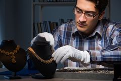 Den unga manliga juveleraren som arbetar på natten i hans seminarium Royaltyfri Foto