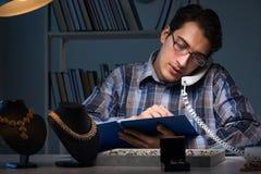 Den unga manliga juveleraren som arbetar på natten i hans seminarium Arkivfoton