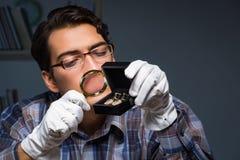 Den unga manliga juveleraren som arbetar på natten i hans seminarium Royaltyfria Foton