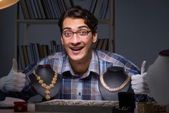Den unga manliga juveleraren som arbetar på natten i hans seminarium Arkivfoto