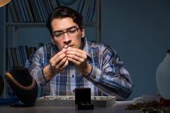 Den unga manliga juveleraren som arbetar på natten i hans seminarium Royaltyfri Bild
