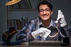 Den unga manliga juveleraren som arbetar på natten i hans seminarium Arkivbilder
