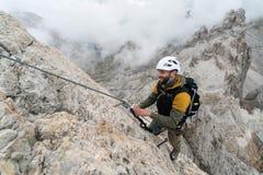 Den unga manliga klättraren på ett brant och utsatt vaggar framsidan som klättrar a via Ferratayoung den stiliga manliga klättrar royaltyfria bilder