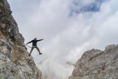 Den unga manliga klättraren på ett brant och utsatt vaggar framsidan som klättrar a via Ferratayoung den stiliga manliga klättrar arkivbild