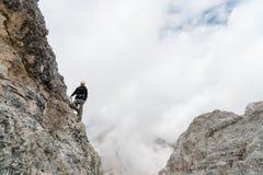 Den unga manliga klättraren på ett brant och utsatt vaggar framsidan som klättrar a via Ferratayoung den stiliga manliga klättrar royaltyfri bild