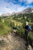 Den unga manliga klättraren ser upp på a via Ferrata i dolomitesna, och många personer står bak honom royaltyfri foto