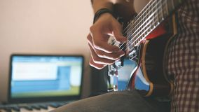 Den unga manliga musikern komponerar och antecknar filmmusiken som spelar gitarren genom att använda datoren, hörlurar och tangen Arkivfoto