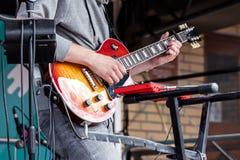Den unga manliga musikern som spelar den electro gitarren under stad, vaggar festen fotografering för bildbyråer