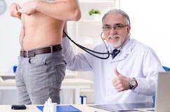 Den unga manliga patienten som besöker den gamla doktorn arkivbilder
