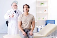 Den unga manliga patienten som besöker den gamla doktorn arkivbild