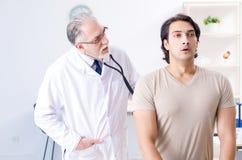 Den unga manliga patienten som bes?ker den gamla doktorn arkivbilder