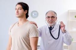 Den unga manliga patienten som bes?ker den gamla doktorn arkivfoton
