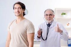 Den unga manliga patienten som bes?ker den gamla doktorn royaltyfri fotografi