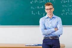 Den unga manliga professorn poserar på skrivbordet Royaltyfria Foton