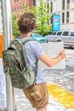 Den unga manliga protesteraren med kaki- kortslutningar och ryggsäcken lutar på ljus pol och håll upp tecken bredvid gatan med tr royaltyfri bild