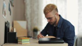 Den unga manliga studenten med stilfull frisyr med exponeringsglas gör anmärkningar på klistermärke på skrivbordtabellen med bärb lager videofilmer