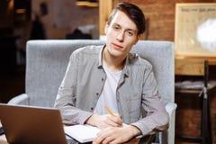Den unga manliga studenten skriver information i en anteckningsbok, förbereder sig för föreläsningar i universitetsområdet, varv  royaltyfri bild