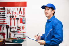 Den unga manliga teknikern på arbete i mekaniker bearbetar lagringsrum royaltyfri bild