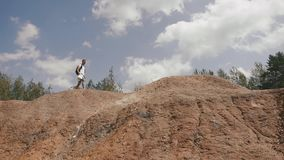 Den unga manliga turisten går på steniga kullar i berg som kontrollerar hans väg med den pappers- översikten lager videofilmer