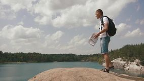 Den unga manliga turisten går på steniga kullar nära sjön i berg som kontrollerar hans väg med den pappers- översikten arkivfilmer