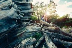 Den unga manliga turisten vilar på en inloggningssommarForest And Enjoy View Of natur royaltyfria foton
