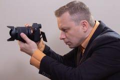 Den unga manliga videopd kameraman, fotograf, skjuter videoen eller tar ett foto p? kameran royaltyfria bilder