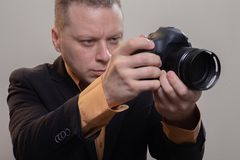 Den unga manliga videopd kameraman, fotograf, skjuter videoen eller tar ett foto p? kameran royaltyfri fotografi
