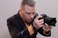 Den unga manliga videopd kameraman, fotograf, skjuter videoen eller tar ett foto p? kameran arkivbilder