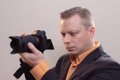 Den unga manliga videopd kameraman, fotograf, skjuter videoen eller tar ett foto p? kameran royaltyfria foton